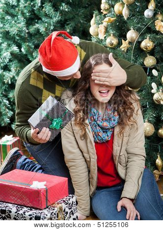 Young man in Santa hat surprising woman with Christmas presents in store