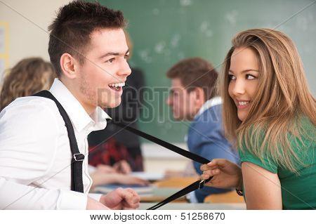 Smiling schoolgirl pulling her colleague's suspenders