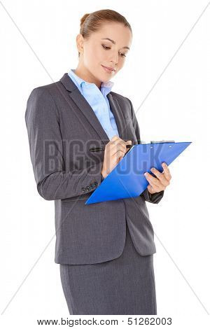 Beautiful stylish young businesswoman standing writing notes on a clipboard reading them with a thoughtful expression  isolated on white