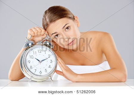 Bored young woman counting down the time sitting at a table clutching a large classic retro style silver metallic alarm clock with bells