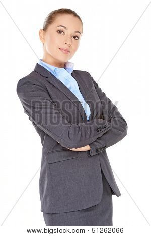 Confident poised young businesswoman standing sideways with her arms folded  isolated on white