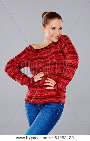 Sexy stylish young woman in a knitted red jersey posing with her hands on her hips giving the camera a playful flirtatious smile