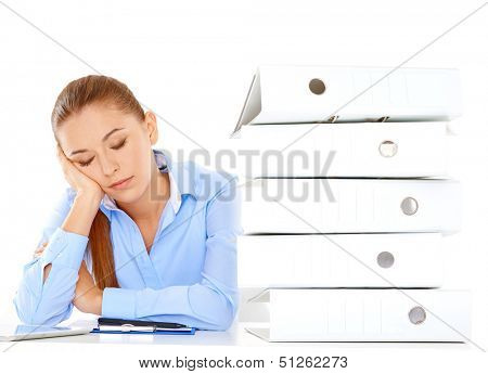 Tired young businesswoman taking a nap at her desk during her lunch break resting her head on her hand alongside a tall stack of office files