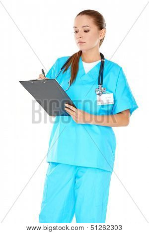 Pretty young nurse in green scrubs standing writing up notes on a clipboard with a serious expression  isolated on white