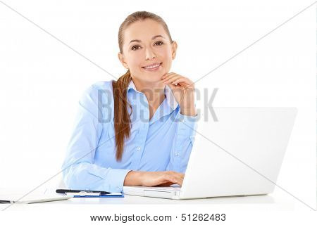Smiling businesswoman sitting at her desk working on a laptop computer against a white background