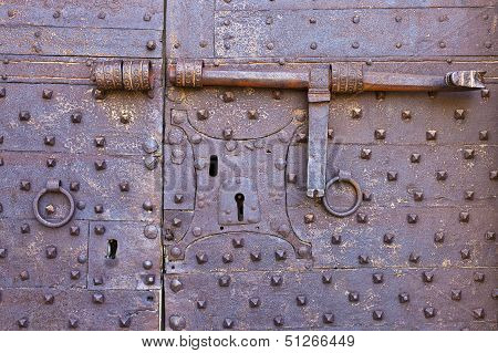 Old And Rusty Metal Door With Many Keyholes