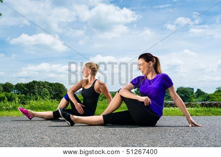 Urban sports - young women doing warming up together before running in the greenfield on a summer day