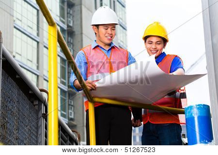 Chinese architect and supervisor point on building site on a construction plan