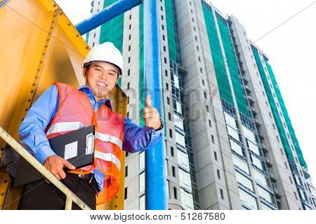 Chinese construction worker or supervisor or architect with clipboard on a building site in Asia