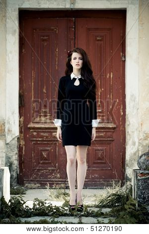 Beautiful young lady in black dress at old manor