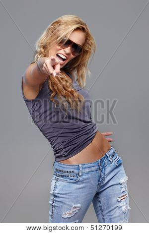 Sexy woman in sunglasses posing on grey background