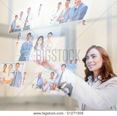Pleased businesswoman selecting pictures on digital screen