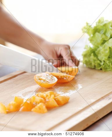 Vegetables being sliced on a board
