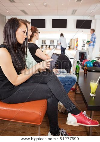 Side view of young woman using digital tablet sitting with friends in bowling club
