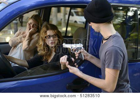 Criminal with gun robbing woman in car