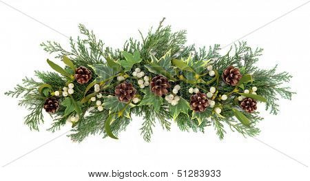 Christmas floral decoration with mistletoe, ivy pine cones and winter greenery over white background.
