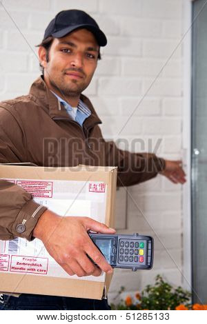 Postal worker, carrying a parcel and a portable ATM rings a doorbell with a cash on delivery service