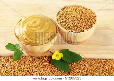 Mustard with seeds and mustard flower on wooden background