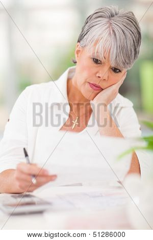 stressed senior woman paying her bills