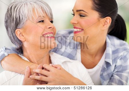 cheerful middle aged mother and young adult daughter looking at each other