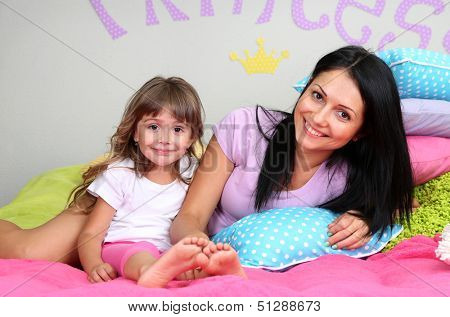 Little girl with mom lying on bed in room on grey wall background