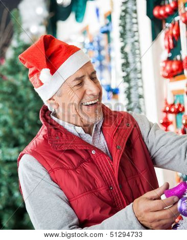 Happy senior male owner in Santa hat working at Christmas store