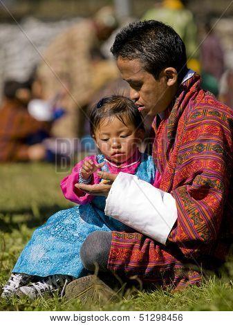 Jakar, Bhutan - October 24, 2010: Unidentified Girl Gets Fruit From Her Father At The Jakar Tsechu O