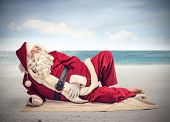 stock photo of beard  - Santa Claus relaxes lying on the beach - JPG