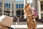 stock photo of buggy  - Trendy modern mother on a city street with a pram - JPG