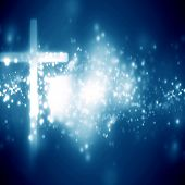 stock photo of glowing  - glowing christian cross on a blue background with some glitters - JPG