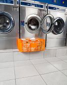 stock photo of laundromat  - Basket of clothes kept in front of open washing machine at laundromat - JPG