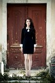 stock photo of manor  - Beautiful young lady in black dress at old manor - JPG