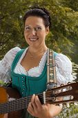 Bavarian woman in dirndl smiling while playing guitar at the lake