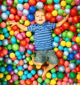 image of pool ball  - Happy child playing at colorful plastic balls playground high view - JPG