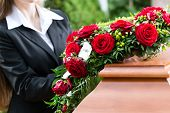 foto of casket  - Mourning woman on funeral with red rose standing at casket or coffin - JPG
