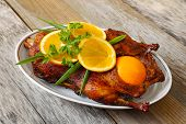 stock photo of roast duck  - Roasted duck with orange on a wood table - JPG