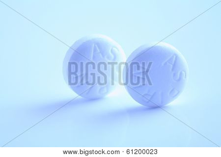 Two circular aspirin pills on blue background