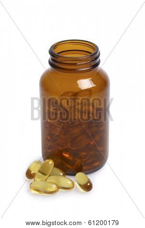 Colored glass bottle of pills with pills in foreground on white background