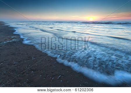 Warm Sunset Over Sand Beach In North Sea