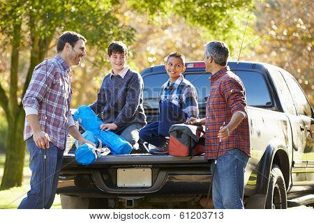 Fathers With Sons Unpacking Truck On Camping Holiday