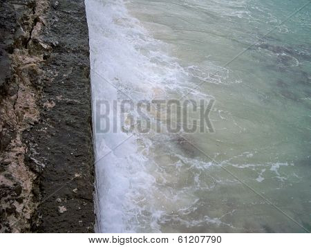 Waves crash against sea wall