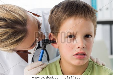 Closeup of little boy being examined by female doctor with otoscope in hospital