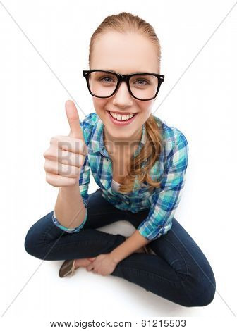 happiness and people concept - smiling young woman in casual clothes and eyeglasses sitiing on floor and showing thumbs up