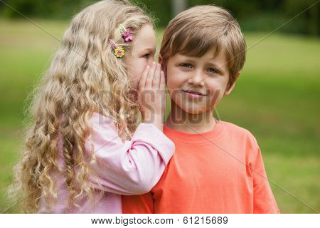Young girl whispering secret into a boy's ear at the park