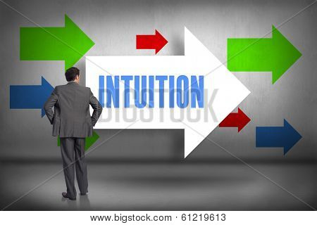 The word intuition and businessman with hands on hips against arrows pointing