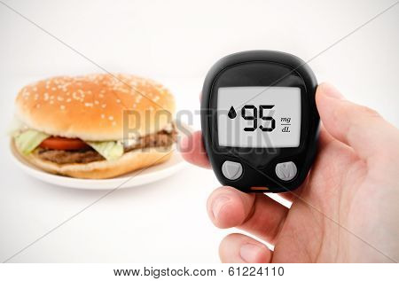 Hand Holding Meter. Diabetes Doing Glucose Level Test. Hamburger In Background