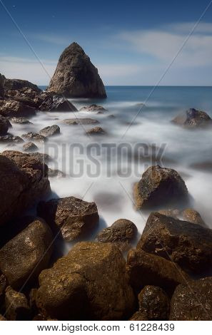 Sea landscape with rocks near the shore waves and foam. Moonlit night and stormy sea. Crimea, Ukraine, Europe