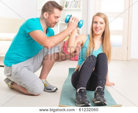 Beautiful young woman doing exercises with dumbbells with personal trainer at home