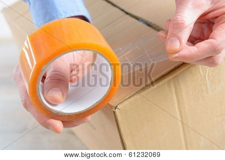 Hands with roll of transparent packaging, adhesive tape on a cardbox