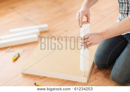 furniture, home and moving concept - close up of male hands assemblying legs to table